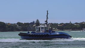 Tugboat works at Captain Cook Wharf in Ports of Auckland, New Zealand. Tugboat, small, strongly built vessel, used to guide large oceangoing ships into and out stock footage