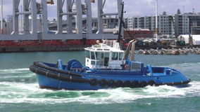 Tugboat works at Captain Cook Wharf in Ports of Auckland, New Zealand. Tugboat, small, strongly built vessel, used to guide large oceangoing ships into and out stock video
