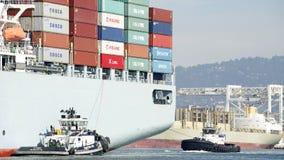 Tugboats ζ-ΤΡΙΑ και ΕΠΑΝΑΣΤΑΣΗ που βοηθά COSCO GUANGZHOU Στοκ Φωτογραφία