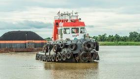 Tugboats τραβούν τη φορτηγίδα βαριών φορτίων του μαύρου άνθρακα Στοκ Εικόνες