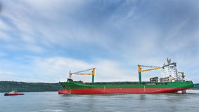 Tugboats, assisting container cargo ship to harbor. Stock Photos