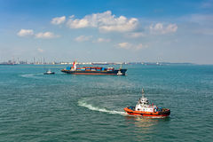 Tugboats assisting container ship Royalty Free Stock Images