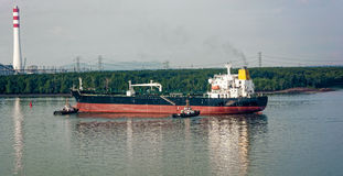 Tugboats assisting oil tanker. Tugboats tugs help turn around a large oil tanker on the way out of the harbor Stock Photos