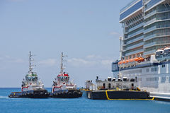 Tugboats and Barge by Cruise Ship. Two tugboats and a barge tied up to a cruise ship Stock Photography