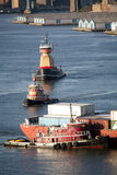 Tugboats and cargo ship in East River Royalty Free Stock Photos