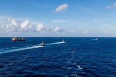 Tugboats Żegluje Za Pomarańczowym tankowem Fotografia Stock