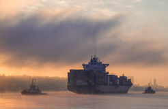 Tugboats pull and push freighter at sunrise Stock Images