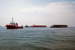 Tugs and barges in Singapore anchorage. Several small tug boats seen towing large barges in Singapore anchorage Stock Photo