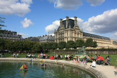 The Tuilerie and the Louvre in Paris. Tourists playing with children in the public park Les Tuileries in Paris. Le Louvre inthe background Royalty Free Stock Photography