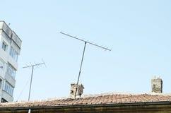 Tuiles de toit oranges, cheminée et vieille antenne de l'analogue TV Photographie stock libre de droits