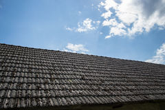 Tuiles de toiture âgées sur la vieille maison dans le village Beaucoup de mousse sur le toit carrelé du taudis contre le ciel nua images stock