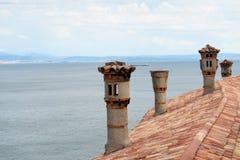 Tuiles et cheminées de toit sur le château de Duino Photo stock