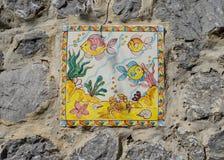 Tuiles peintes à la main avec des poissons sur des murs de rue de Vietri Images stock