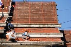 Tuiles se réunissantes de Roofer jusqu'au dessus du toit non fini de temple Photos stock