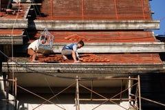 Tuiles se réunissantes de Roofer jusqu'au dessus du toit non fini de temple Photographie stock