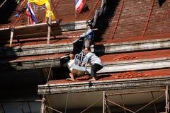 Tuiles se réunissantes de Roofer jusqu'au dessus du toit non fini de temple Photo libre de droits