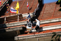 Tuiles se réunissantes de Roofer jusqu'au dessus du toit non fini de temple Images libres de droits