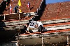 Tuiles se réunissantes de Roofer jusqu'au dessus du toit non fini de temple Image stock