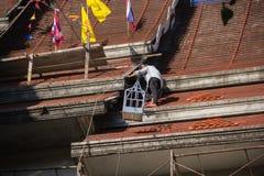 Tuiles se réunissantes de Roofer jusqu'au dessus du toit non fini de temple Image libre de droits