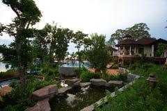 Tuin bij het overzees Zwembad, zonlanterfanters naast de tuin en gebouwen Stock Foto's