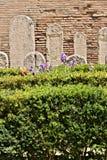 Tuin met bukshouthagen en Roman grafstenen in wit marmer stock afbeelding