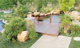 Tuin met houten pergola en vijver Stock Fotografie