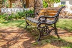 Tuin met latjes shade.CR2 van de gietijzer de houten bank royalty-vrije stock afbeeldingen