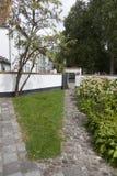 Tuin met portiek en witte geschilderde muur van begijnhof in Belg Stock Foto's