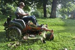 Tuinarchitect bij het berijden van grasmaaimachine Stock Foto