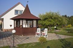 Tuinhuis met rode dak en tuin Stock Afbeelding