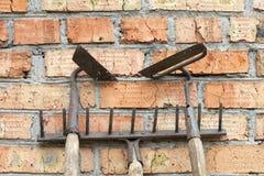 Tuinhulpmiddelen: oude en roestige harken en schoffels tegen de oude doorstane bakstenen muur Royalty-vrije Stock Foto