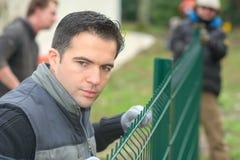 Tuinierend team die tuinomheining opzetten royalty-vrije stock afbeeldingen