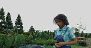 Tuinlieden die in plantenkwekerij lopen stock videobeelden