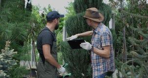 Tuinlieden die tablet en scharen gebruiken stock footage