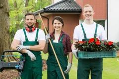 Tuinlieden met het tuinieren hulpmiddelen en bloemen royalty-vrije stock afbeeldingen