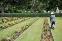 tuinman die aan het gazon in een begraafplaats met grafstenen op de achtergrond werken Royalty-vrije Stock Afbeelding