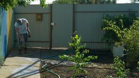 Tuinman die concrete gang in tuin na het water geven van bomen en installaties vegen stock videobeelden
