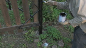 Tuinman die de ijzeromheining schilderen die zwarte verf gebruiken stock videobeelden