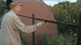 Tuinman die de ijzeromheining schilderen die zwarte verf gebruiken stock video