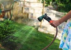 tuinman die de tuin water geeft Stock Afbeelding