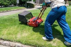 Tuinman die een grasmaaimachine in tuin met behulp van stock foto