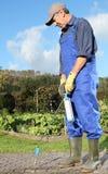Tuinman die mos verwijderen bij Straatstenen met vlampottenbakker Stock Foto