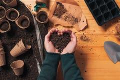 Tuinmanhandvol van grond in tot een kom gevormde handen stock afbeeldingen