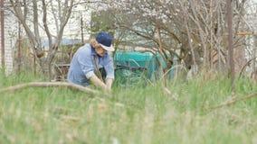 Tuinmanvrouw die droog gras schoonmaken terwijl het tuinieren het werk in tuinbinnenplaats stock footage