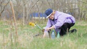 Tuinmanvrouw die plastic fles voor bloemenzaailing met behulp van in tuinbinnenplaats stock videobeelden