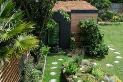 Tuinruimte, groene terugtocht met bij vriendschappelijke, het leven sedumdak in goed opgeslagen, rijpe tuin Stock Foto