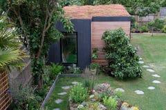 Tuinruimte, groene terugtocht met bij vriendschappelijke, het leven sedumdak in goed opgeslagen, rijpe tuin Stock Foto's