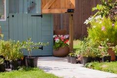 Tuinweg die tot een geschilderde loods leiden Stock Afbeelding