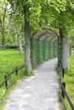 Tuinweg met groene boog Stock Afbeelding