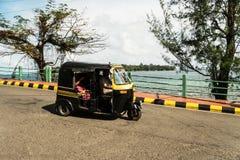 Tuk Tuk везет пассажиров на дороге против моря стоковое фото rf